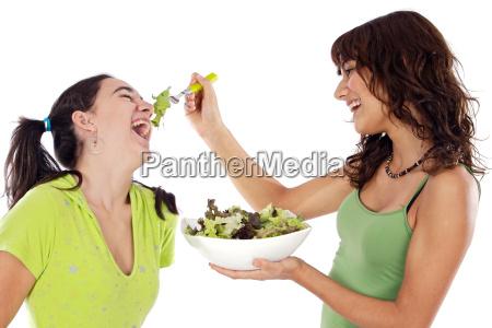zwei schoene maedchen mit einem salat