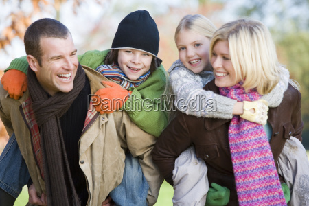 parents outdoors piggybacking two young children