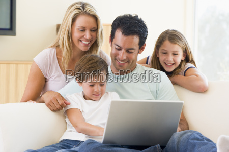 family in living room with laptop