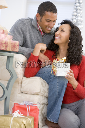 husband and wife affectionately exchanging christmas