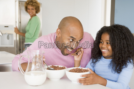 father sitting with daughter as she