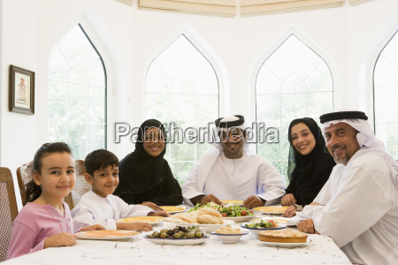 family sitting at dinner table smiling
