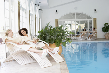 women relaxing around pool at spa