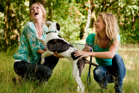 sisters are playing with the dog