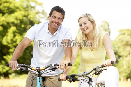 paar reiten fahrraeder in der landschaft
