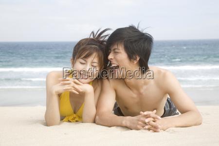 japanese couple lying on a beach