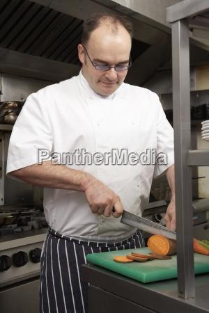 male chef preparing vegetables in restaurant