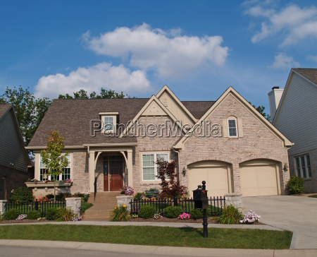 small beige brick home with two