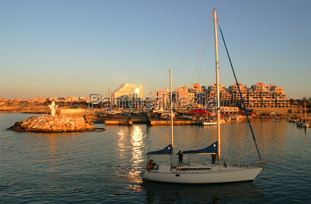 yacht entering marina at sunset in