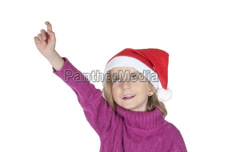 kleines maedchen mit weihnachtsmuetze zeigt nach