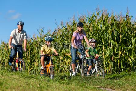 familie faehrt fahrrad im sommer