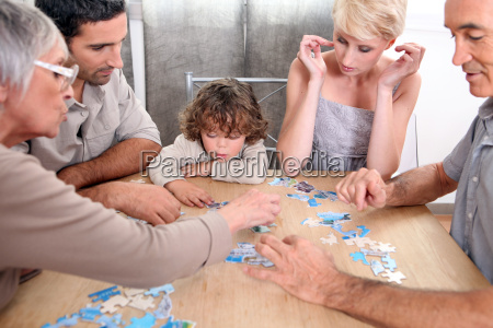 family completing jig saw puzzle