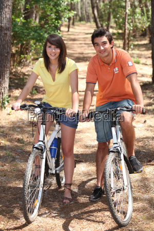 young couple riding bikes in a