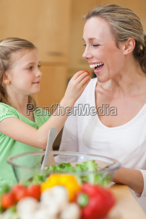 girl feeding her mother with salad