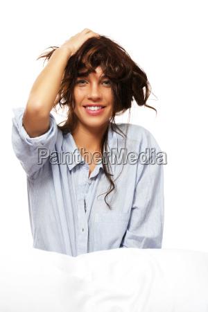 glueckliche frau im schlafanzug haelt ihre