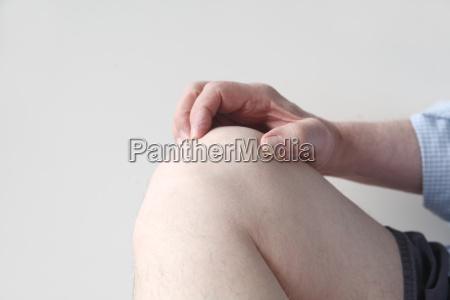 man grasps his sore knee