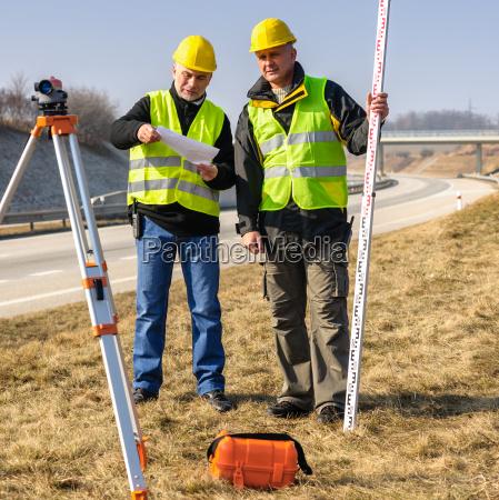 geodesist two man theodolite stand highway