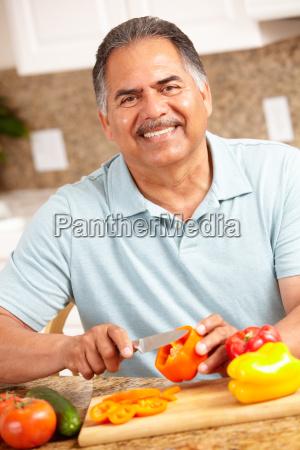 senior man chopping vegetables