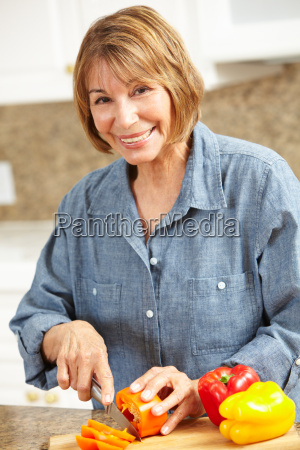 mid age woman chopping vegetables