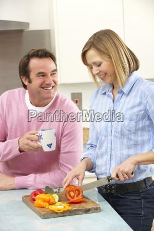 mature couple preparing meal in domestic