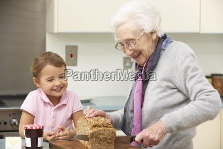 grandmother and granddaughter preparing food in