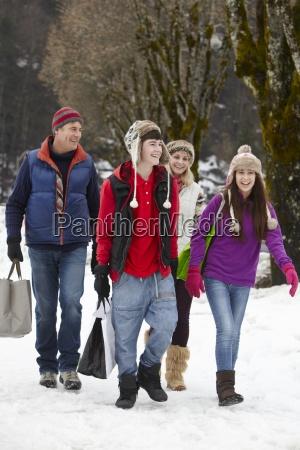 teenage family carrying shopping walking along