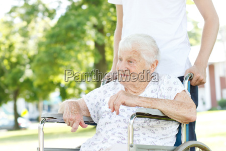 senior women in wheelchair with caretaker