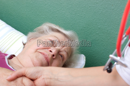patientin begruesst im bett liegend aerztin