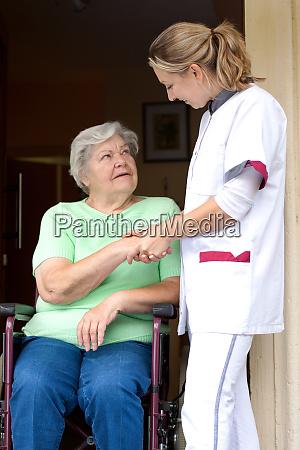pflegerin reicht patientin im rollstuhl die