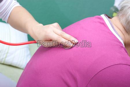 aerztin untersucht seniorin mit stethoskop