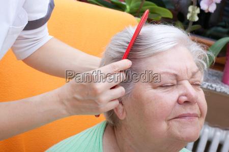 pflegerin kaemmt seniorin durch ihr haar
