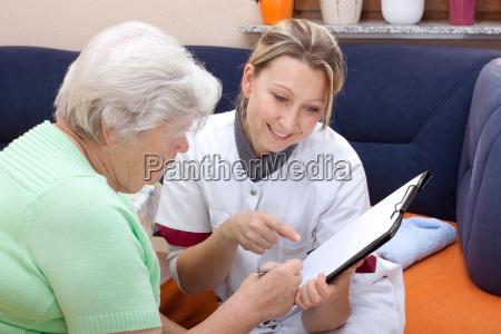 seniorin und pflegerin sitzen beieinander daten