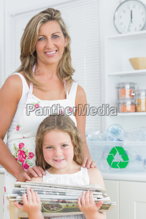 smiling mother standing behind her daughter