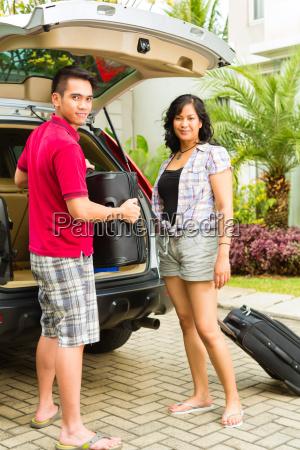 asiatisches paar ist gluecklich vor auto