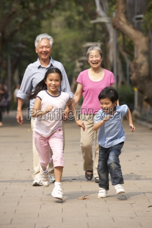 chinese grandparents walking through park with
