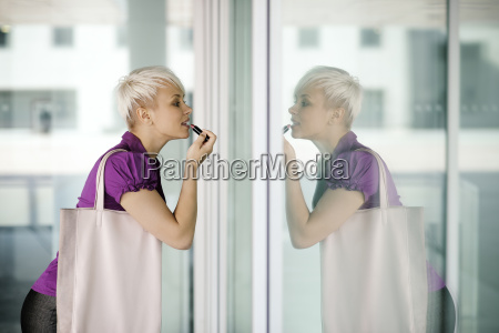 young business woman applying makeup in