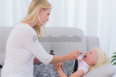 mother giving her daughter medicine on