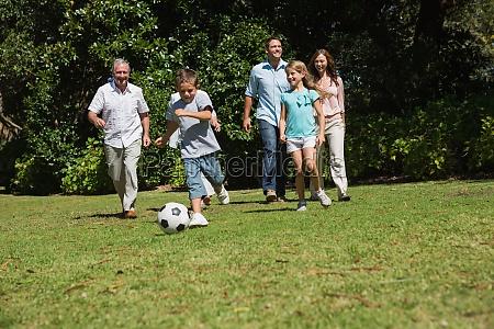 happy multi generation family playing football