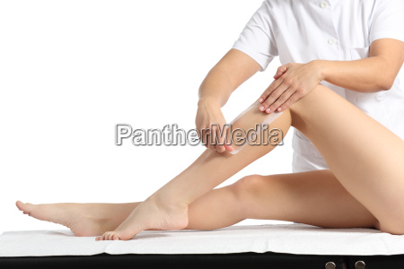 beautician waxing a beautiful smooth woman