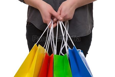 eine frau haelt bunte einkaufstaschen fuers