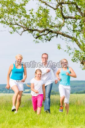 familie rennt ueber feld oder wiese