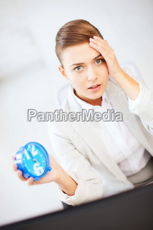 stressed businesswoman holding clock