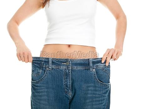 slim woman pulling oversized jeans
