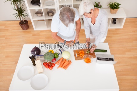 middle aged couple preparing a meal