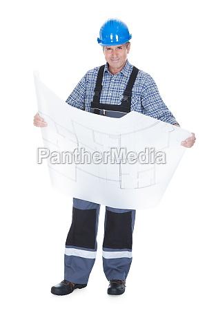 male architect holding blueprint