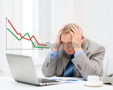 upset older businessman with laptop and