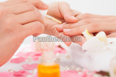 manicurist applying nail varnish