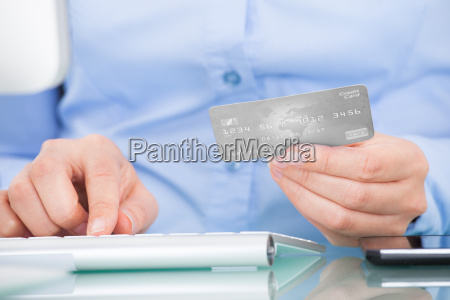 person holding credit card using computer