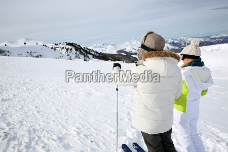 back view of skiers looking at