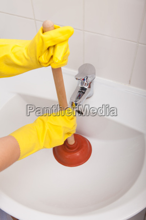 persons hand pressing plunger in sink